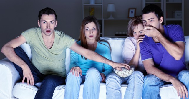 Young attractive people are watching TV at home